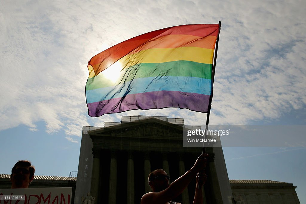 Gay rights activist Vin Testa of DC waves a flag in front of the U.S. Supreme Court building June 24, 2013 in Washington DC. The high court is expected to rule this week on some high profile decisions including California's Proposition 8, the controversial ballot initiative that defines marriage as between a man and a woman.