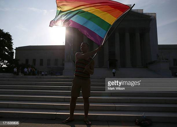 Gay rights activist Vin Testa of DC waves a flag in front of the US Supreme Court building June 26 2013 in Washington DC Today the high court is...