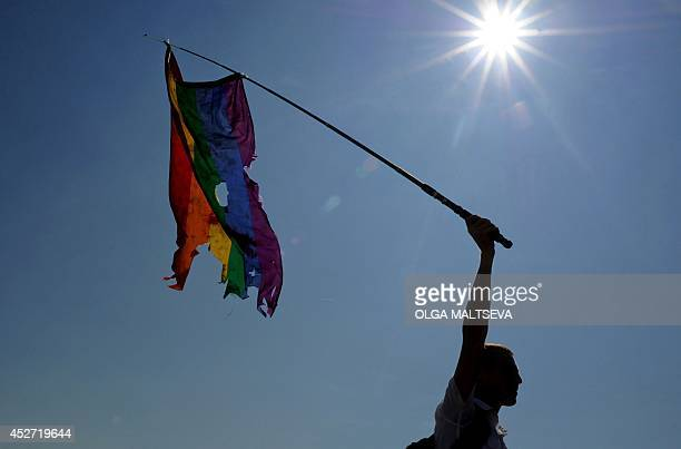 A gay rights activist waves a damaged rainbow flag during a gay pride in St Petersburg on July 26 2014 AFP PHOTO / OLGA MALTSEVA