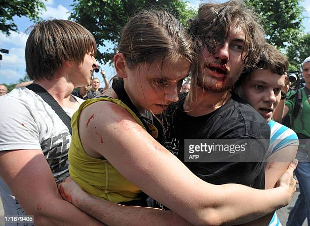 Gay rights activists embrace each other after clashes with antigay demonstrators during a gay pride event in St Petersburg on June 29 2013 Russian...