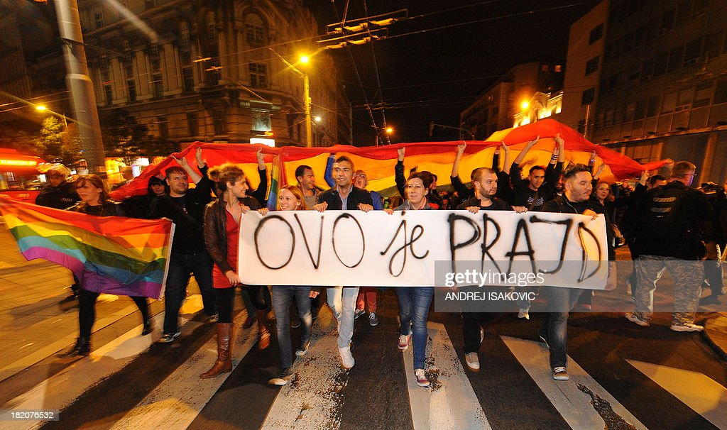 Gay rights activists hold a banner reading 'This is pride' as they demonstrate on late September 27, 2013 in Belgrade. Serbia on September 27, 2013 banned Gay Pride for the third year running, saying the risk of allowing the parade to go ahead was too high. Following the ban, a few hundred gay activists gathered before Serbian government building late on September 27 carrying a huge banner that read 'This is pride.' Escorted by dozens of policemen in anti-riot gear, the group then marched throughout downtown Belgrade to the Serbian parliament building, holding a huge flag in rainbow colours.