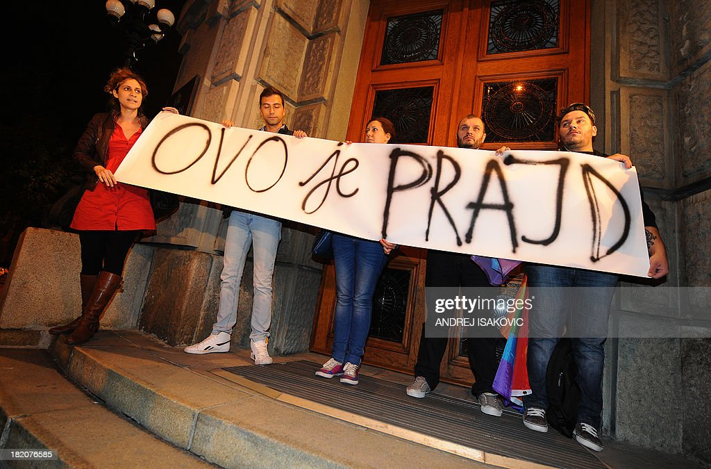 Gay rights activists hold a banner reading 'This is pride' in front of a building of the Serbian government on late September 27, 2013 in Belgrade. Serbia on September 27, 2013 banned Gay Pride for the third year running, saying the risk of allowing the parade to go ahead was too high. Following the ban, a few hundred gay activists gathered before Serbian government building late on September 27 carrying a huge banner that read 'This is pride.' Escorted by dozens of policemen in anti-riot gear, the group then marched throughout downtown Belgrade to the Serbian parliament building, holding a huge flag in rainbow colours.
