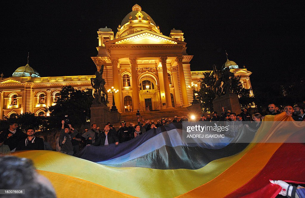Gay rights activists hold a rainbow flag as they demonstrate in front of the Serbian Parliament on late September 27, 2013 in Belgrade. Serbia on September 27, 2013 banned Gay Pride for the third year running, saying the risk of allowing the parade to go ahead was too high. Following the ban, a few hundred gay activists gathered before Serbian government building late on September 27 carrying a huge banner that read 'This is pride.' Escorted by dozens of policemen in anti-riot gear, the group then marched throughout downtown Belgrade to the Serbian parliament building, holding a huge flag in rainbow colours.