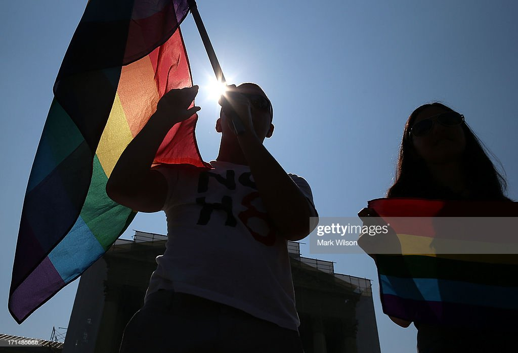 Gay rights activists hold flags outside the U.S. Supreme Court building on June 25, 2013 in Washington, DC. The high court convened again today to rule on some high profile decisions including including two on gay marriage and one on voting rights.