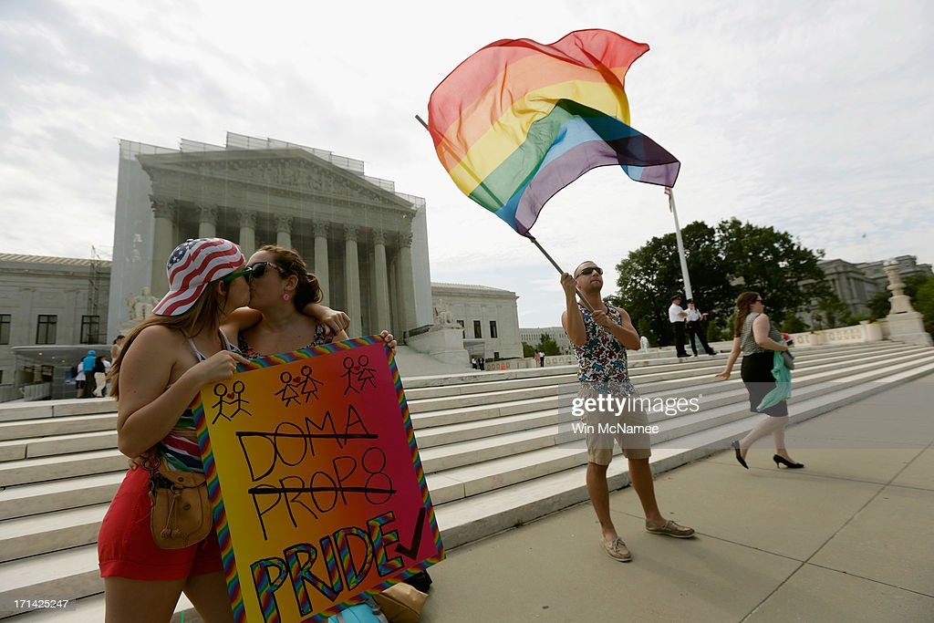 Gay rights activists Meghan Cleary (L) and Sarah Beth Alcabes from Berkley, CA kiss front of the U.S. Supreme Court building as Vin Testa of DC waves a flag June 24, 2013 in Washington DC. The high court is expected to rule this week on some high profile decisions including California's Proposition 8, the controversial ballot initiative that defines marriage as between a man and a woman.