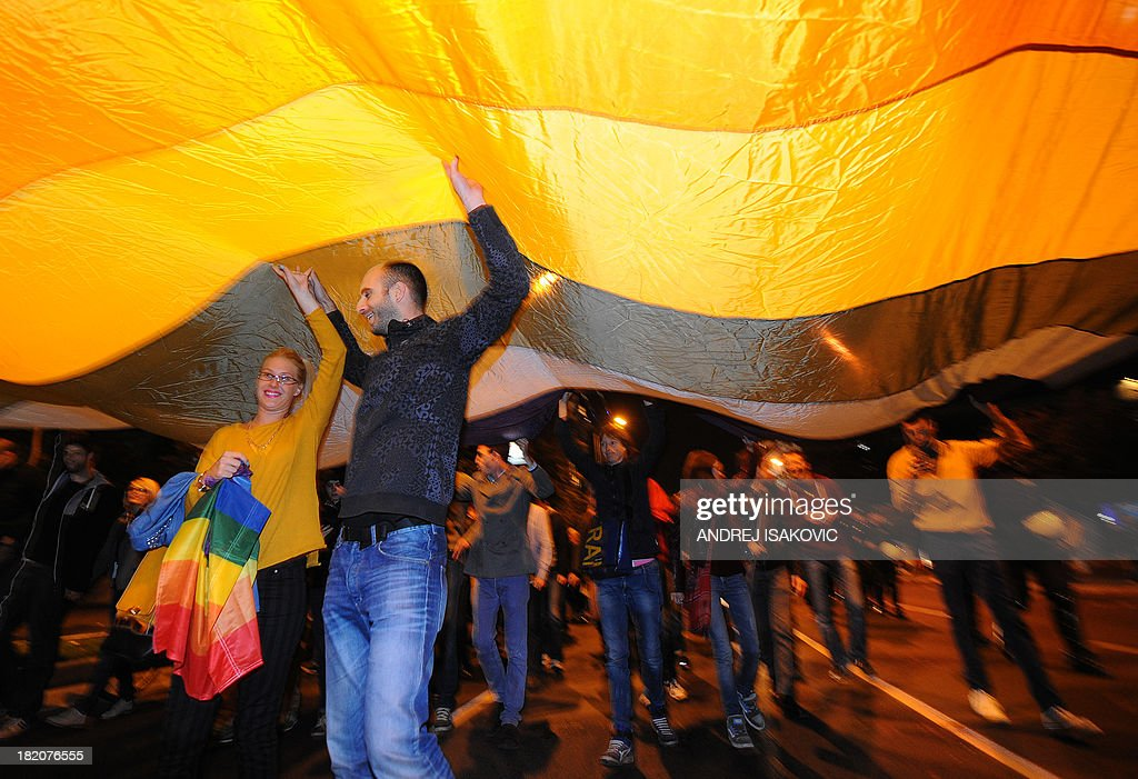 Gay rights activists wave a giant rainbow flag near a building of the Serbian government on late September 27, 2013 in Belgrade. Serbia on September 27, 2013 banned Gay Pride for the third year running, saying the risk of allowing the parade to go ahead was too high. Following the ban, a few hundred gay activists gathered before Serbian government building late on September 27 carrying a huge banner that read 'This is pride.' Escorted by dozens of policemen in anti-riot gear, the group then marched throughout downtown Belgrade to the Serbian parliament building, holding a huge flag in rainbow colours.
