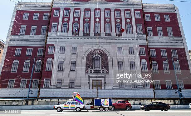 Gay rights activists wave rainbow flags from a car during a protest held in front of the Mayor's office in central Moscow on May 31 2014 Riot police...