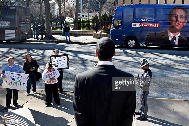 Gay rights atavists stand on the sidewalk while Santorum supporters speak outside the Georgia State Capitol Building March 5 2012 in Atlanta Georgia...