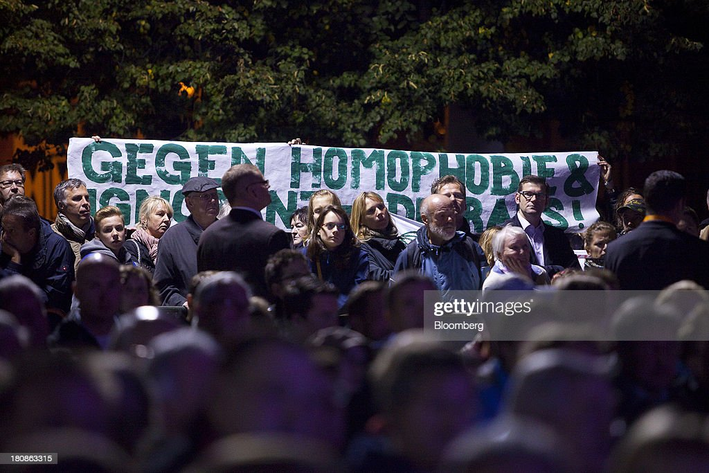 Gay rights protestors hold up a banner during a Christian Democratic Union (CDU) election rally in Potsdam, Germany, on Monday, Sept. 16, 2013. Delayed plans for a financial transaction tax in 11 European states would get a fresh push if Chancellor Angela Merkel enters a coalition with the Social Democrats after Sept. 22 German elections, top SPD members said. Photographer: Krisztian Bocsi/Bloomberg via Getty Images
