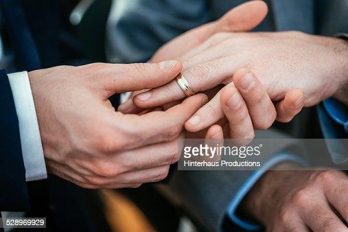 Gay Wedding Groom Placing Ring On Husband