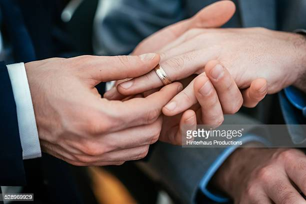 Gay Wedding Groom Placing Ring On Husband