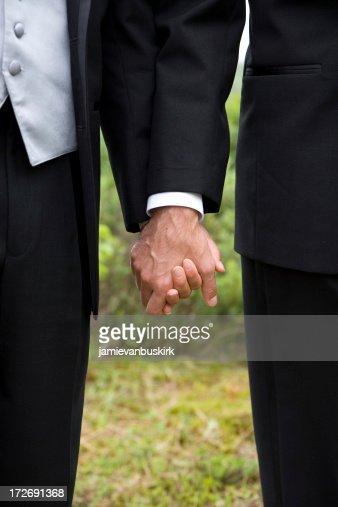 Gay wedding grooms holding hands