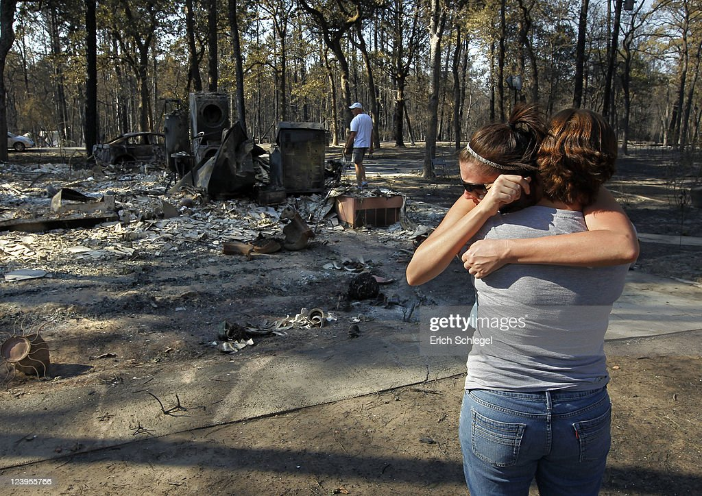Gaye Jaco (front) hugs her stepdaughter Jennifer Leaver upon returning to their burned down home on the east side of Lake Bastop on September 6, 2011 outside Bastrop, Texas. Several large wildfires have been devastating Bastrop County for the last two days.