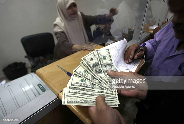 Gaza civil servant shows banknotes in the Omer AlMukhtar post office after receiving delayed salaries on October 29 2014 in Gaza City Gaza Thousands...