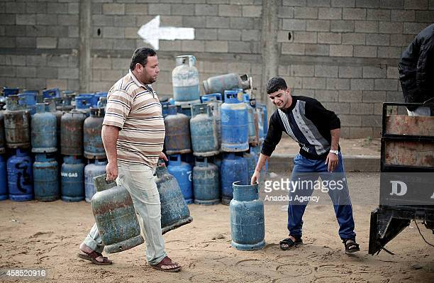 Gazan workers carrying bottled gas at a gas filling center in Gaza City Gaza on November 4 2014 The ongoing electricity crisis in the Gaza Strip has...