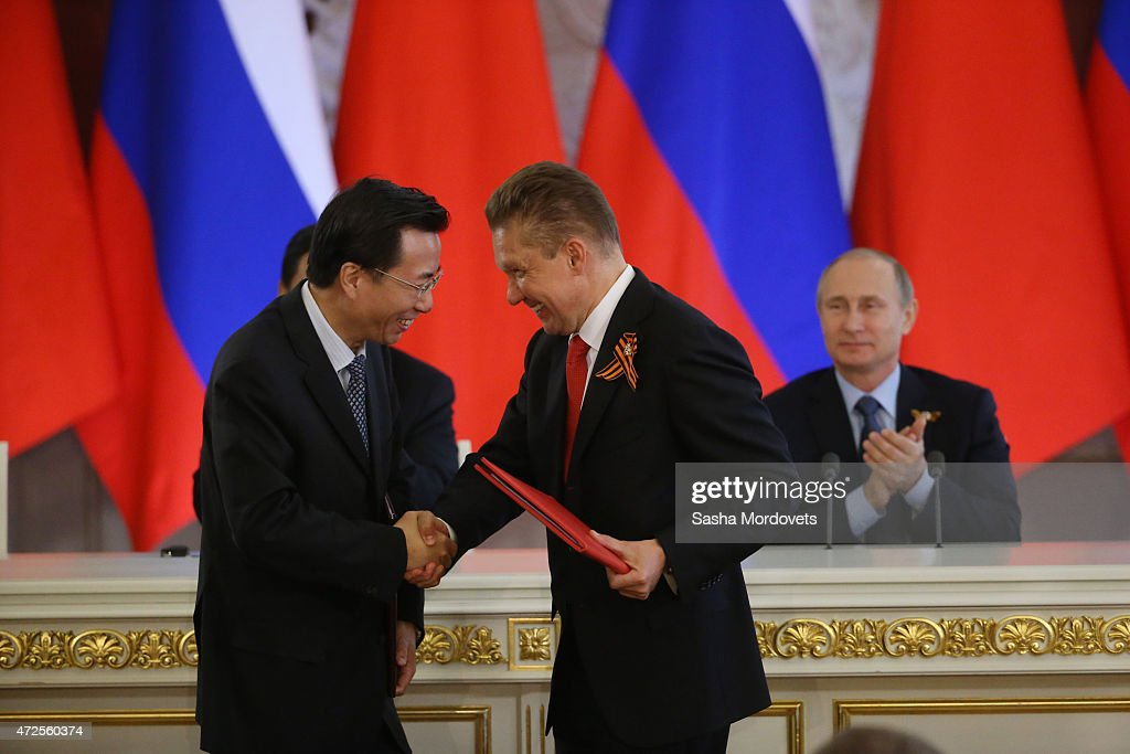 Gazprom's CEO Alexei Miller (R) shakes hands with Vice-President of Chinese National Oil and Gaz Corporation Van Dunjing (L) as they exchange documents during Russian-Chinese talks as Russian President Vladimir Putin looks on in the Grand Kremlin Palace on May 8, 2015 in Moscow, Russia. Xi Jinping is on a two-day visit to Moscow and plans to attend the Victory Day military parade which will take place at Moscow's Red Square on May 9 to celebrate 70 years after the victory in WWII.