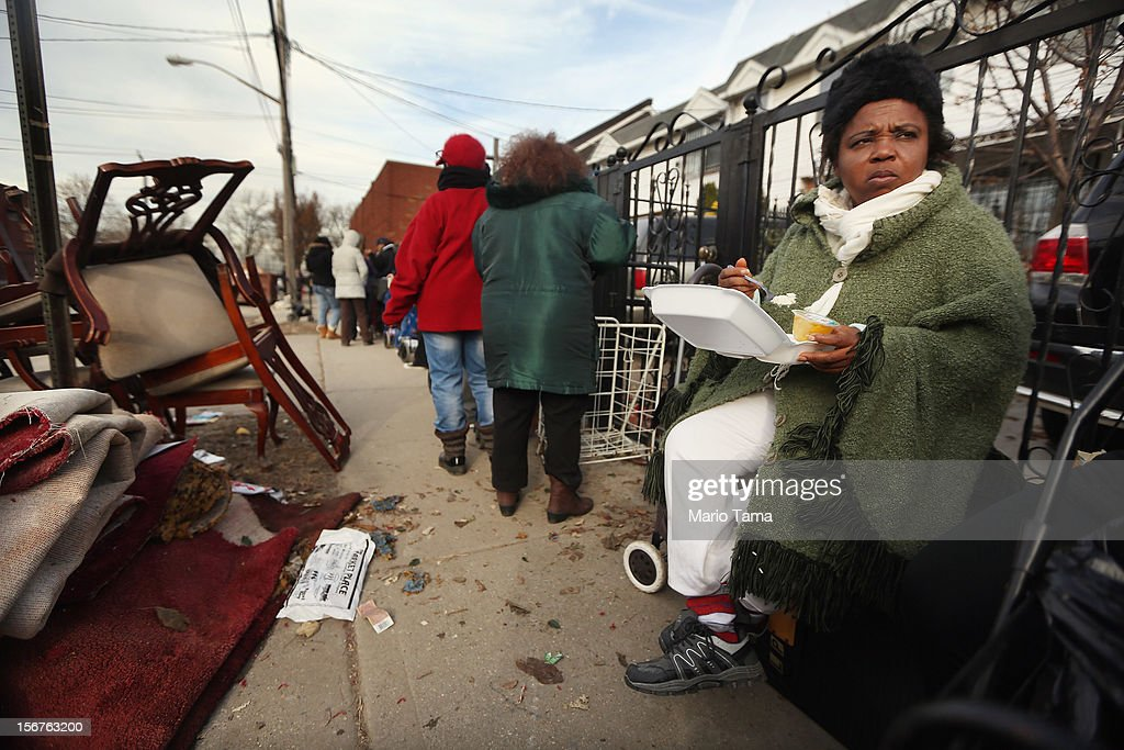 Gbemmy Woods (R) waits on line to obtain food and other items from a distribution point near flood debris in the Coney Island neighborhood on November 20, 2012 in the Brooklyn borough of New York City. The Coney Island area was hard hit by Superstorm Sandy and Woods lost power for two weeks.