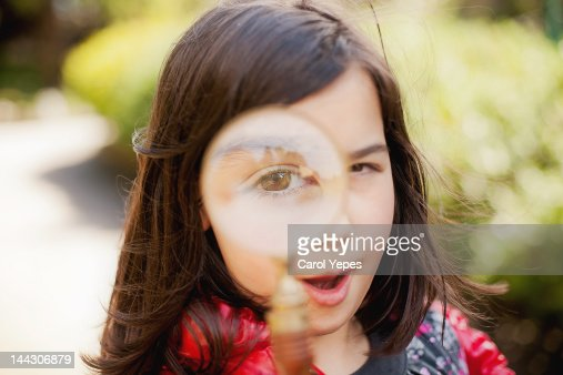Gbirl looking through magnifying glass : Stock Photo
