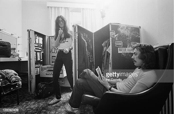 Geddy Lee singer and bassist and Neil Peart drummer of Canadian rock band Rush pictured backstage with Peart sitting in an armchair reading a book...