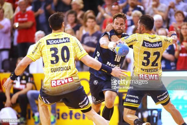 Gedeon Guardiola and Alexander Petersson of RheinNeckarLoewen fight for the ball with Thomas Mogensen of SG Flensburg Handewitt during the Game SG...