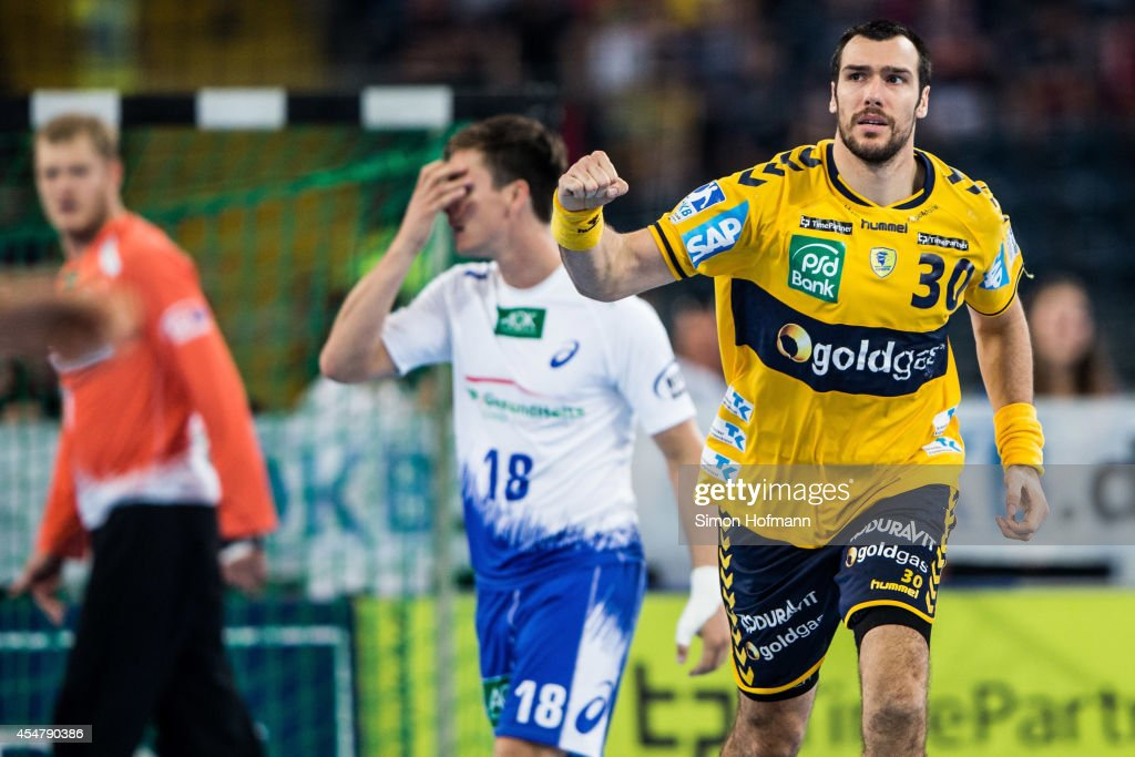 Gedeon Guardiola of Rhein-Neckar Loewen celebrates as <a gi-track='captionPersonalityLinkClicked' href=/galleries/search?phrase=Hans+Lindberg&family=editorial&specificpeople=863614 ng-click='$event.stopPropagation()'>Hans Lindberg</a> of Hamburg (C) reacts during the DKB HBL match between Rhein-Neckar Loewen and HSV Hamburg at Commerzbank-Arena on September 6, 2014 in Frankfurt am Main, Germany.