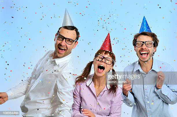 Geek group with party hats on head, confetti, toothy smiling