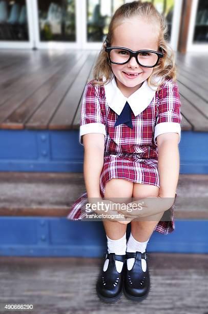 Geeky Mädchen mit Brille sitzt auf der Treppe