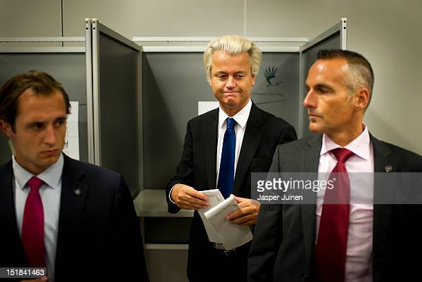 Geert Wilders of the Freedom Party walks in between security men to cast his ballot for the Dutch parliamentary elections in a polling station on...
