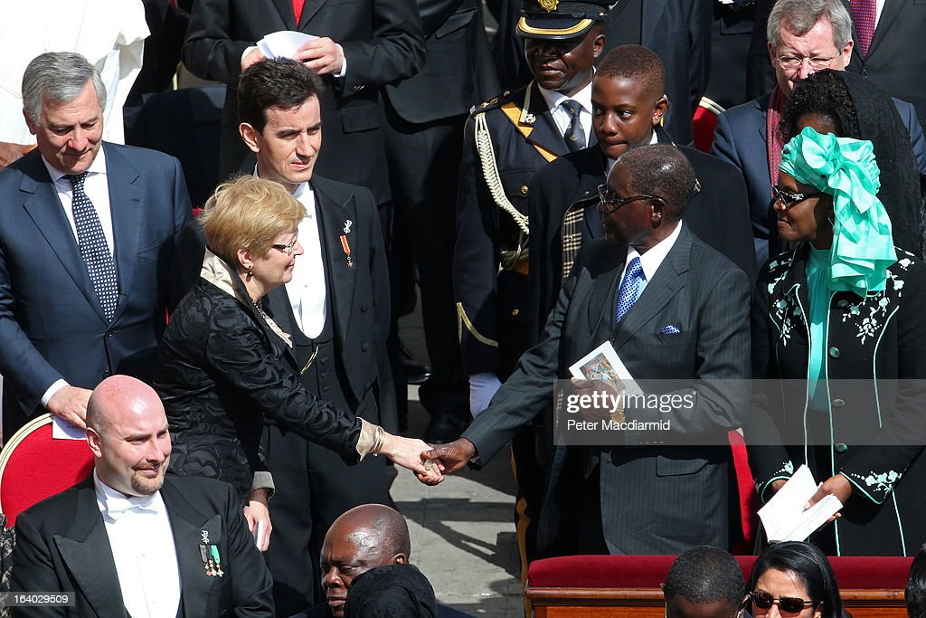 Geertrui Windels, wife of the President of the European Council, Herman van Rompuy, shakes hands with Zimbabwe President <a gi-track='captionPersonalityLinkClicked' href=/galleries/search?phrase=Robert+Mugabe&family=editorial&specificpeople=214676 ng-click='$event.stopPropagation()'>Robert Mugabe</a> during the Inauguration Mass for Pope Francis in St Peter's Square on March 19, 2013 in Vatican City, Vatican. The mass is being held in front of an expected crowd of up to one million pilgrims and faithful who have filled the square and the surrounding streets to see the former Cardinal of Buenos Aires officially take up his role as pontiff. Pope Francis' inauguration takes place in front of Cardinals and spiritual leaders as well as heads of state from around the world.