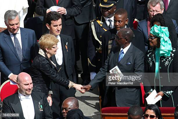 Geertrui Windels wife of the President of the European Council Herman van Rompuy shakes hands with Zimbabwe President Robert Mugabe during the...