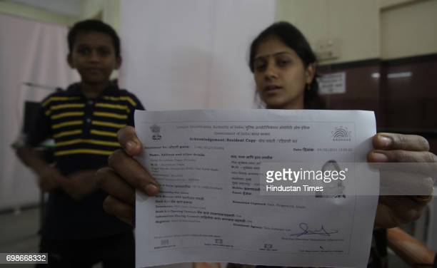 Geeta shows her acknowledgement copy after getting Iris scanned at UID enrollment at Kawalmathe BMC school in Mumbai