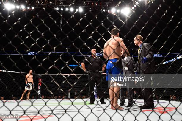 Gegard Mousasi of the Netherlands waits as Chris Weidman is examined by doctors in their middleweight bout during the UFC 210 event at the KeyBank...