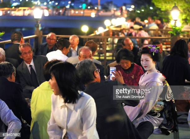 Geiko and maiko entertain guests as a riverside terrace resstaurant 'NoryoDoko' open at Kamogawa River on May 1 2017 in Kyoto Japan The terrace...
