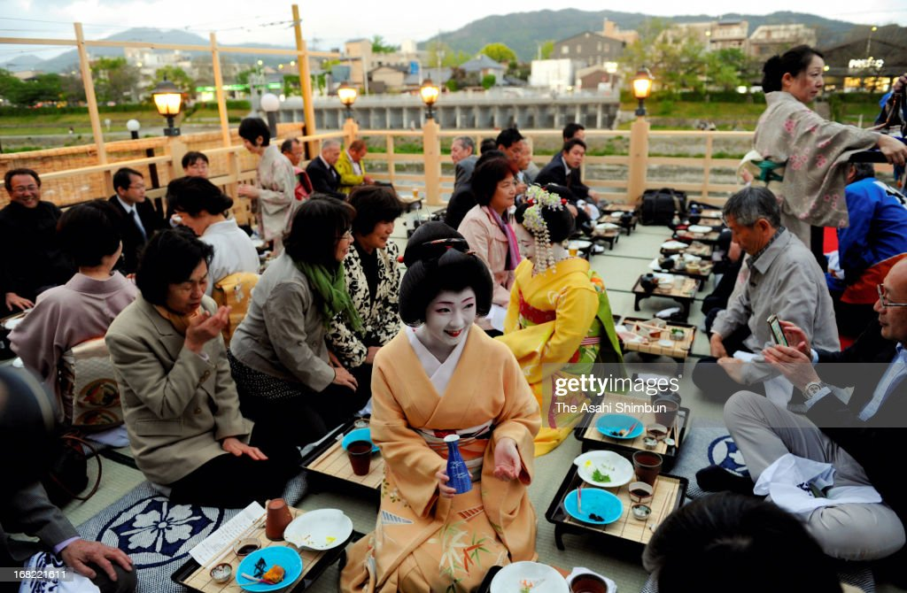Geiko and maiko serve Japanese sake to the customers at the opening of open terrace restaurant on May 1, 2013 in Kyoto, Japan. The terrace restaurants at Kamogawa River are the one of popular seasonal landscape in Kyoto, will be opened until September 30.