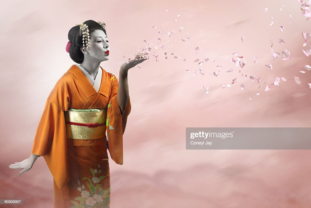 Geisha blowing many cherry blossom petals