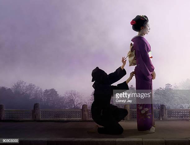 Geisha having her kimono fixed by a servant