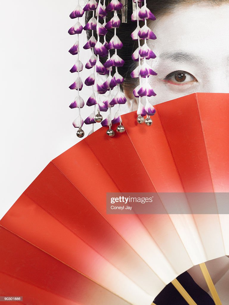 Geisha holding fan in front of face