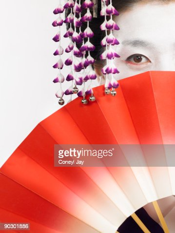 Geisha holding fan in front of face : Stock Photo
