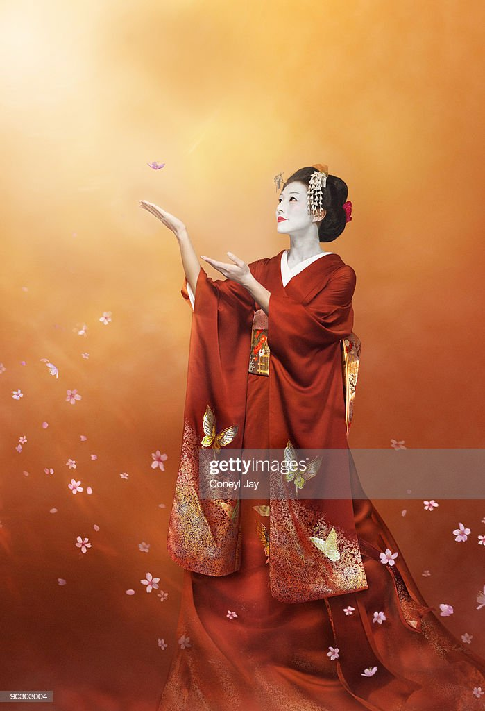 Geisha in long red kimono catching a cherry blosso