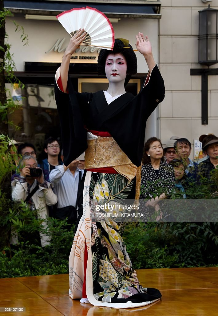 A geisha performs a traditional dance on a stage during the Ginza 'Yanagi' festival at the Ginza shopping district in Tokyo on May 5, 2016. Geishas working in the area displayed their skills for holiday shoppers to promote their 'Azuma Odori,' a traditional dance event taking place later this month. / AFP / TOSHIFUMI