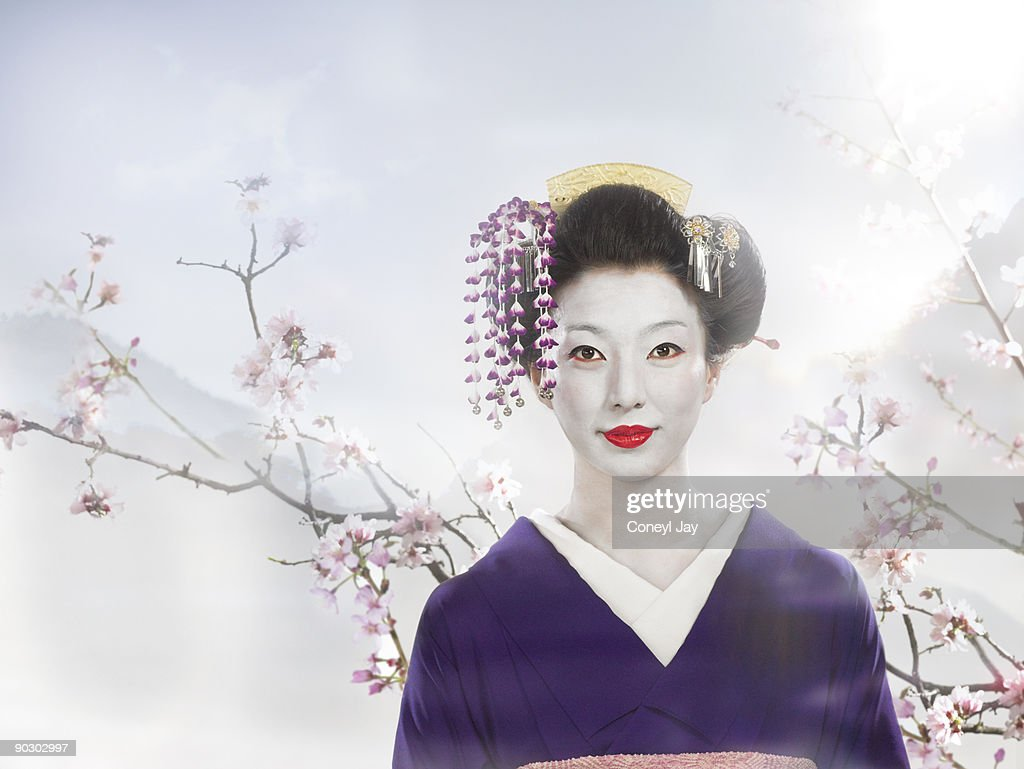 Geisha standing in front of cherry blossoms and mo