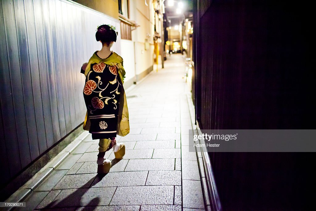 A geisha walking on a secluded path at night.