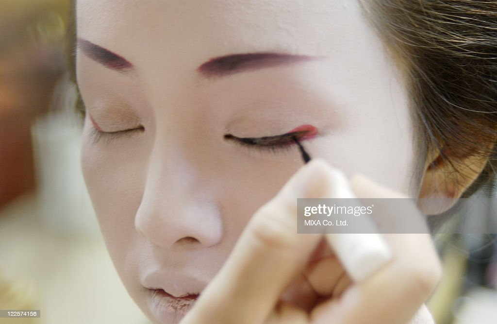 A Geisha woman applying makeup