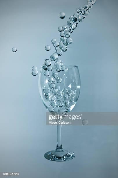 Gel balls falling into glass