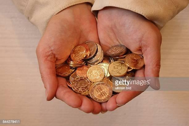 Geld Euro und Cent Muenzen in den Haenden