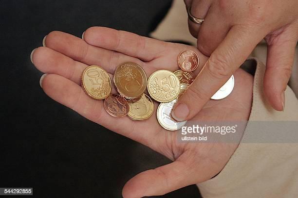 Geld Kleingeld Wechselgeld Euro und Cent Muenzen in einer Hand