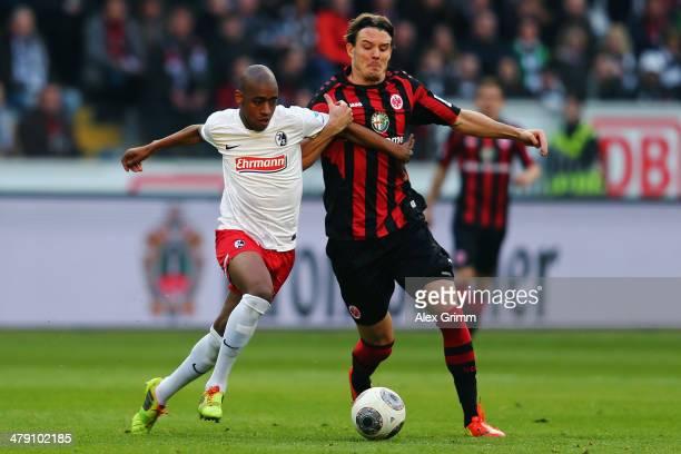 Gelson Fernandes of Freiburg is challenged by Alexander Meier of Frankfurt during the Bundesliga match between Eintracht Frankfurt and SC Freiburg at...