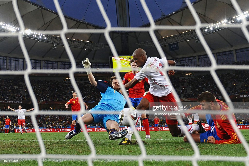 <a gi-track='captionPersonalityLinkClicked' href=/galleries/search?phrase=Gelson+Fernandes&family=editorial&specificpeople=2971817 ng-click='$event.stopPropagation()'>Gelson Fernandes</a> of Switzerland scores the first goal under pressure from <a gi-track='captionPersonalityLinkClicked' href=/galleries/search?phrase=Iker+Casillas&family=editorial&specificpeople=215446 ng-click='$event.stopPropagation()'>Iker Casillas</a> and <a gi-track='captionPersonalityLinkClicked' href=/galleries/search?phrase=Gerard+Pique&family=editorial&specificpeople=227191 ng-click='$event.stopPropagation()'>Gerard Pique</a> of Spain during the 2010 FIFA World Cup South Africa Group H match between Spain and Switzerland at Durban Stadium on June 16, 2010 in Durban, South Africa.