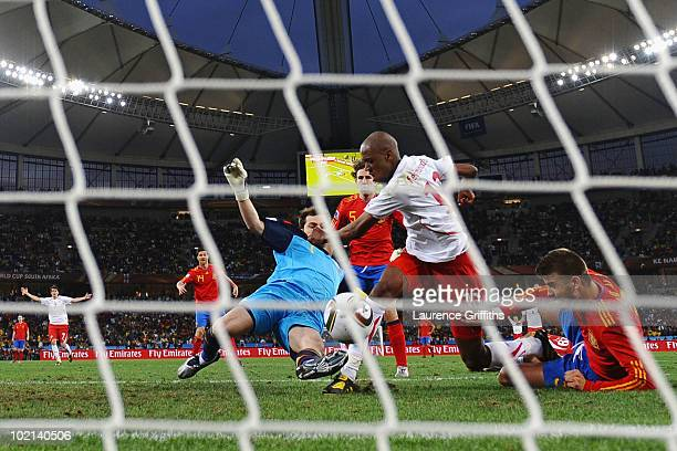 Gelson Fernandes of Switzerland scores the first goal under pressure from Iker Casillas and Gerard Pique of Spain during the 2010 FIFA World Cup...
