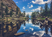 Perfectly still water on Gem Lake with reflection of blue sky, clouds, mountains, and trees, Estes Park, Colorado